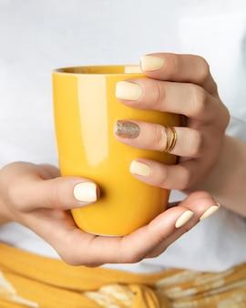 Frauenhände mit gelbem glänzendem nageldesign, der tasse hält.