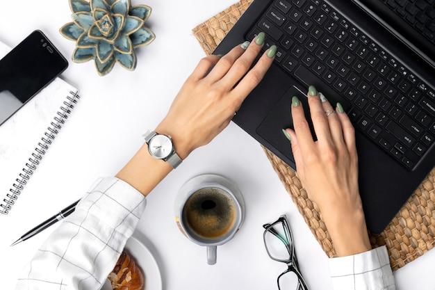 Frauenhände mit grüner frühlingssommermaniküre, die auf laptop schreibt