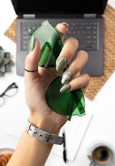 Frauenhände mit grüner frühlingssommermaniküre, die sonnenbrille hält