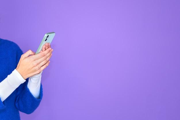 Frauenhände mit handy. detail der hände, die telefon halten und tippen. isolierter lila hintergrund. mädchen, das blauen pullover trägt. grünes telefon.