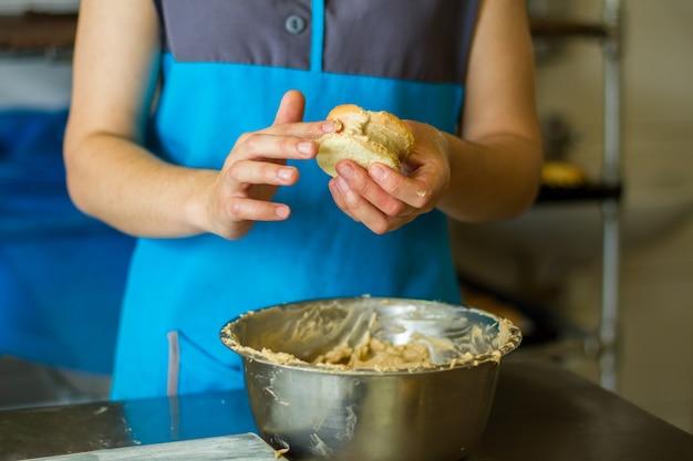 Frauenhände mit kekssandwich. kekse und schüssel mit vanillepudding. angestellter eines konditorei-cafés. arbeitszeiten in der küche.