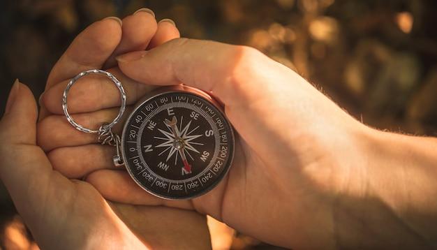 Frauenhände mit kompass im wald, nahaufnahmefoto