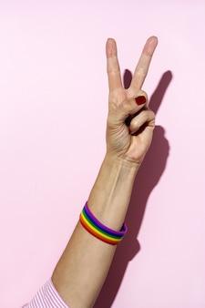Frauenhände mit lgbt-armband auf rosa hintergrund