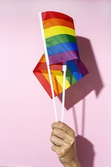 Frauenhände mit lgbt-flagge auf rosa hintergrund