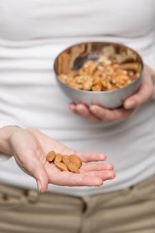 Frauenhände mit mandel und schüssel gemischter nüsse
