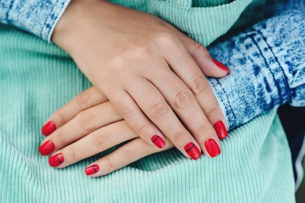 Frauenhände mit nagellack. hipster-mädchen mit jeansjacke, streetstyle.