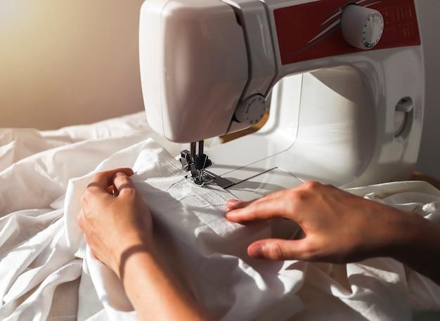 Frauenhände mit natürlichem baumwollstoff-arbeitsprozess an der nähmaschine, die mit textil arbeitet