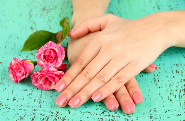 Frauenhände mit rosa maniküre und blumen, auf farbigem hintergrund