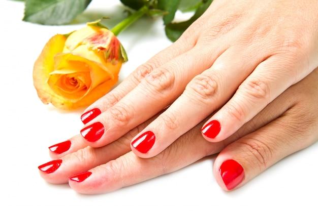 Frauenhände mit roter maniküre und stiegen