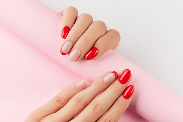 Frauenhände mit roter moderner maniküre über weißen wandmaniküre-designtrends