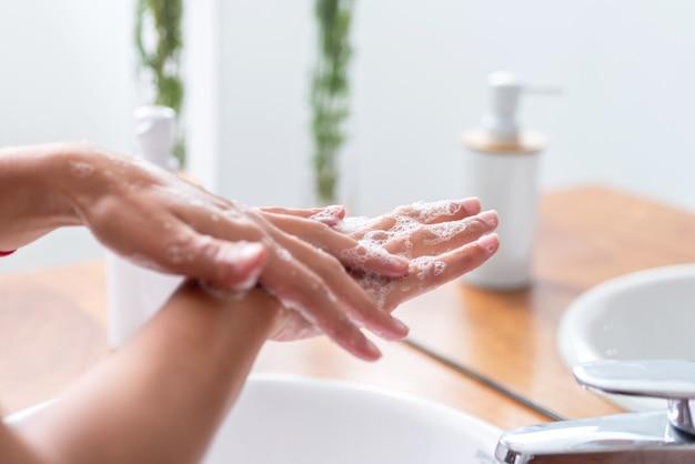 Frauenhände mit seife und händewaschen unter dem wasserhahn