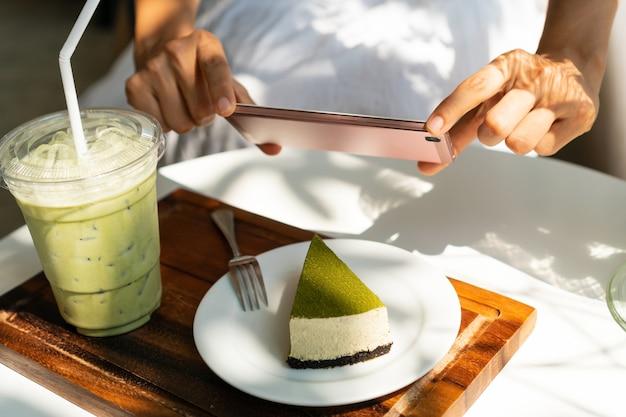 Frauenhände mit smartphone, um ein foto von matcha-käsekuchen mit gefrorenem matcha-latte im café zu machen?