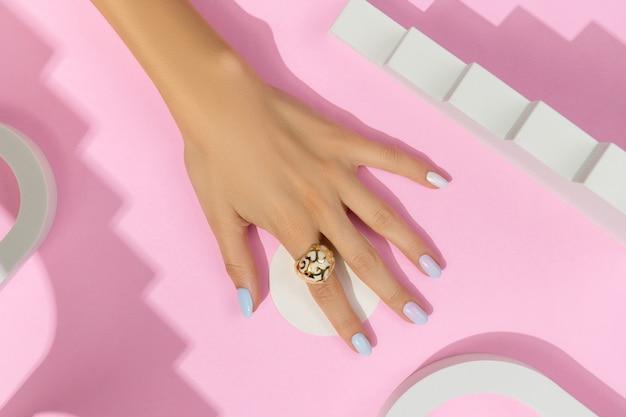 Frauenhände mit trendiger maniküre auf rosa oberfläche. sommernageldesign