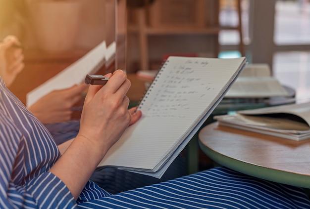 Frauenhände nahaufnahme mit stift und planer, der den tag plant, notizen zu machen und in notizbuch zu schreiben