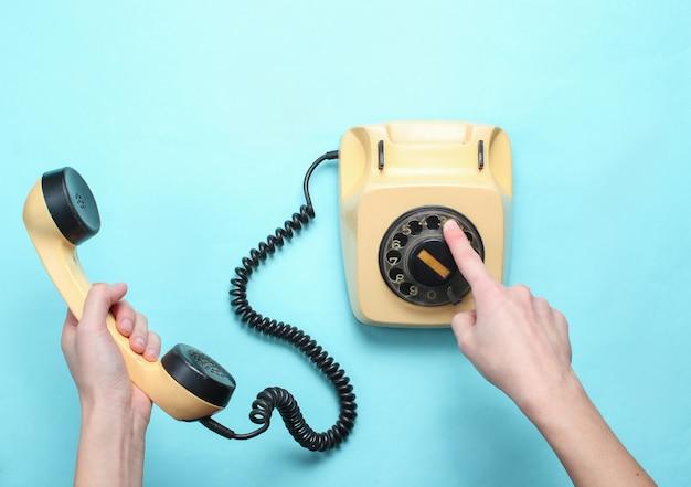 Frauenhände nehmen die nummer des drehtelefons auf und halten das mobilteil auf blauem pastellhintergrund. draufsicht, minimalismus