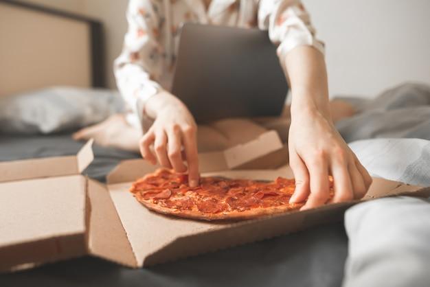 Frauenhände nehmen ein stück pizza aus einer schachtel und sitzen mit einem laptop auf einem bett.