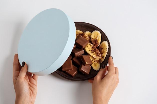 Frauenhände öffnen schachtel mit schokolade und banane auf weiß