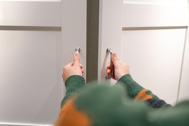 Frauenhände öffnen schrankkabinettholztür