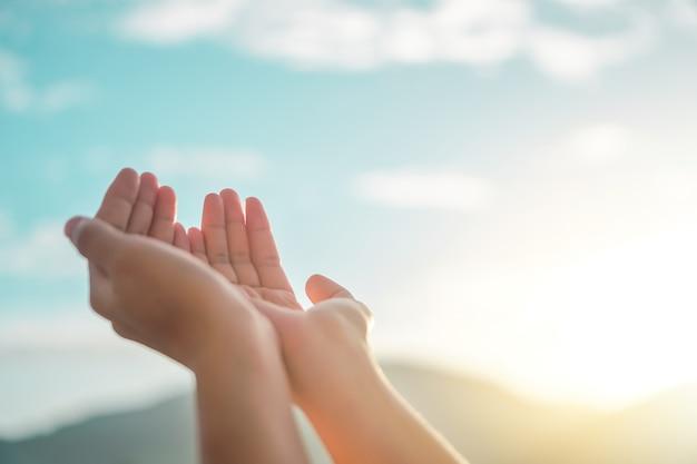 Frauenhände platzieren zusammen wie das beten vor dem grünen hintergrund der natur.