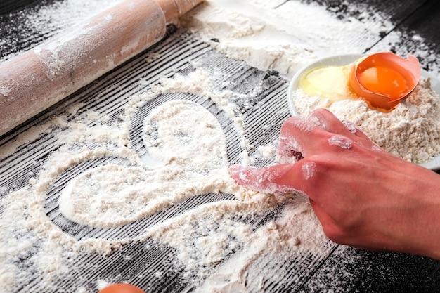Frauenhände rollen den teig auf einem mit mehl bestreuten schwarzen tisch aus.
