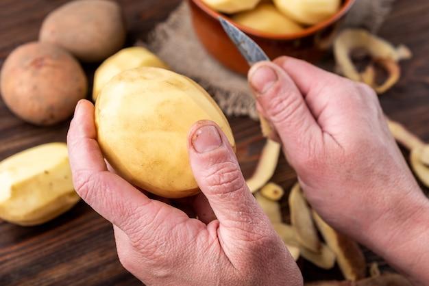 Frauenhände schälen kartoffel. kartoffeln auf holzoberfläche reinigen. lebensmittel zum kochen reparieren.