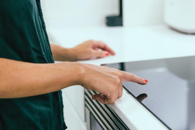 Frauenhände schaltet elektrisches kochfeld ein