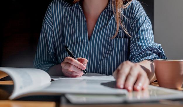 Frauenhände schließen das schreiben mit stift im notizbuch und machen sich notizen aus dem lehrbuch, das mit akademischen b ...