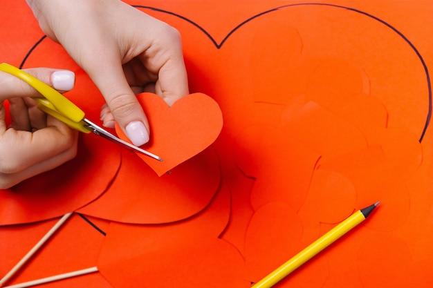 Frauenhände schneiden ein rotes herz auf dem hintergrund eines bleistifts und einer packung herzen aus papier aus.
