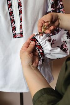 Frauenhände schneiden überschüssigen faden