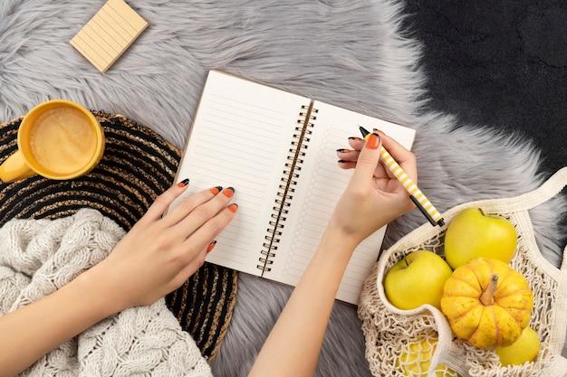 Frauenhände schreiben in notizblock einkaufen, um liste zu tun.