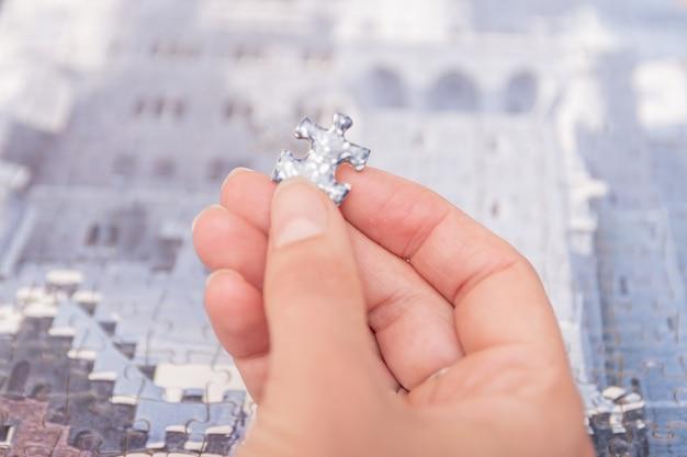 Frauenhände setzen teile eines halb zusammengebauten puzzles