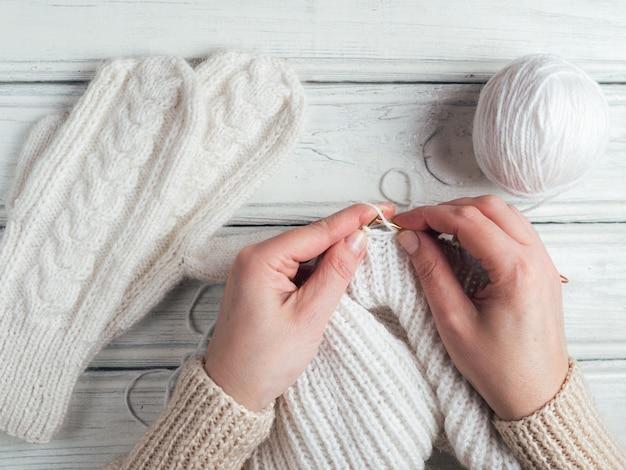 Frauenhände stricken weiße pulloverspeichen