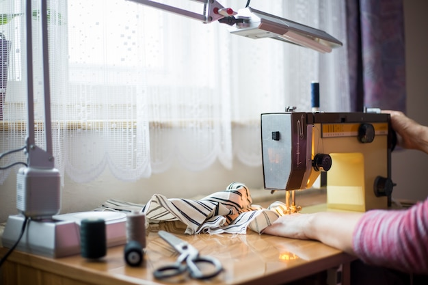 Frauenhände unter verwendung der nähmaschine auf einer nähherstellung, nähprozess