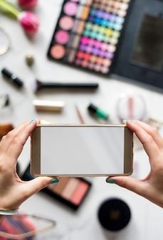 Frauenhände unter verwendung des handys erfassen foto mit kosmetik-hintergrund