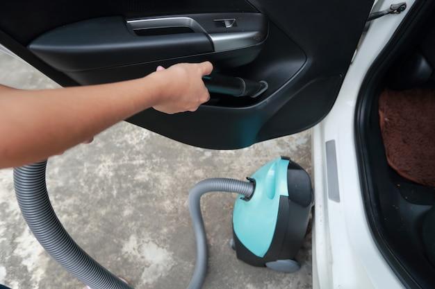 Frauenhände unter verwendung des staubsaugerinnenraumautos