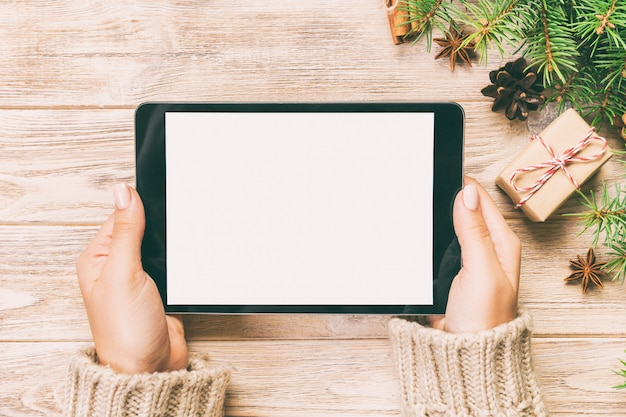 Frauenhände unter verwendung des tablet-computers auf holztisch, cristmas einkaufszeit,