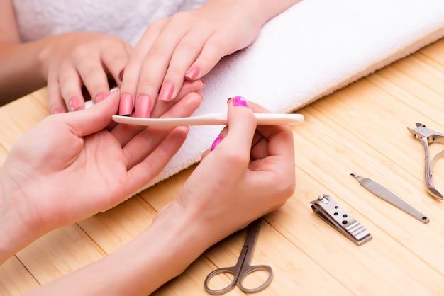 Frauenhände während der maniküresitzung