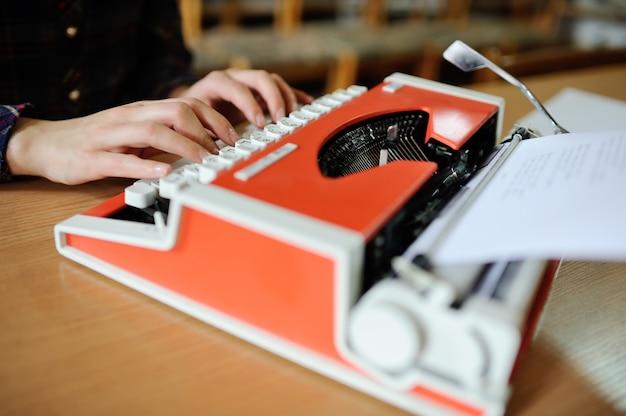 Frauenhände werden auf eine schreibmaschine in roter nahaufnahme gedruckt. bücher schreiben
