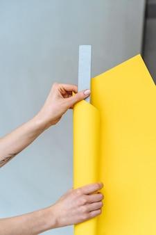 Frauenhände wickeln eine graue nagelfeile in papier