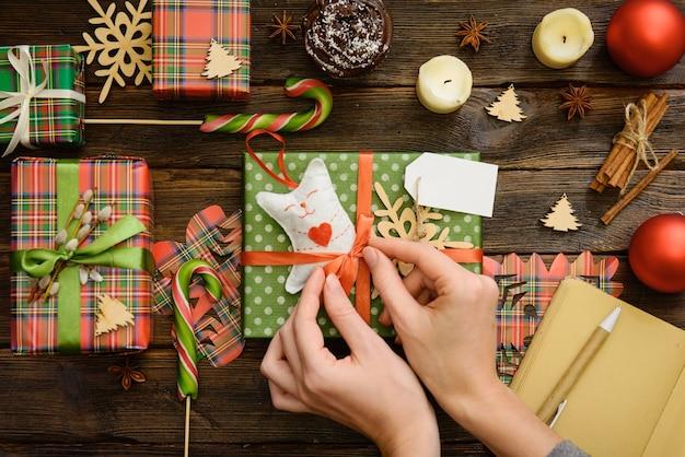 Frauenhände wickeln handgemachte weihnachtsferiengeschenk in papier mit schnurband ein