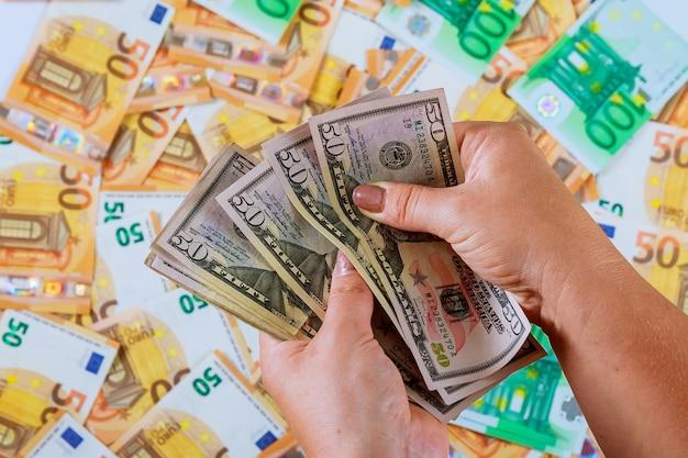 Frauenhände zählen dollar über euro-banknoten.