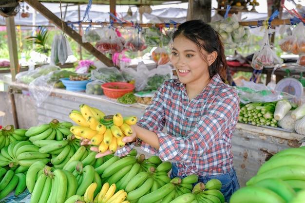 Frauenhändler verkauft gemüse, früchte und bananen, die in einem ländlichen straßenrandgeschäft reifes gelb sind