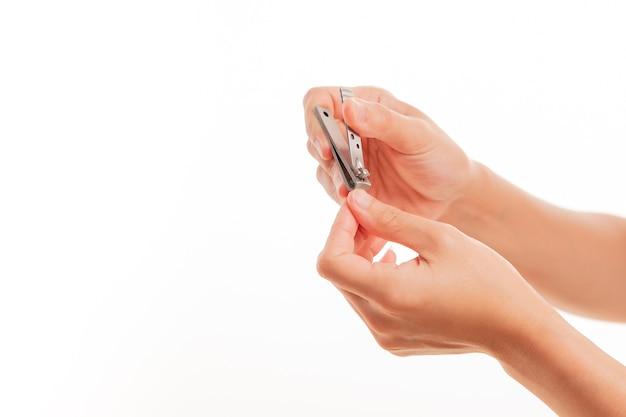 Frauenhand-ausschnittnägel unter verwendung des nagelknipsers auf weißen hintergründen