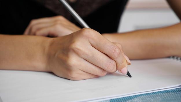 Frauenhand benutzen bleistiftschreiben auf klarem weißem blatt
