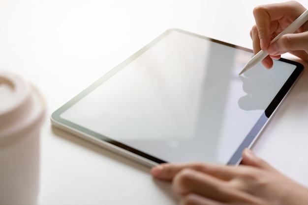 Frauenhand benutzen die tablette auf dem schreibtisch. nehmen sie ihren bildschirm, um werbung zu schalten.
