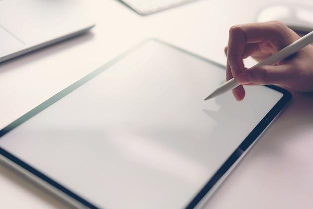 Frauenhand benutzen die tablette auf dem schreibtisch.