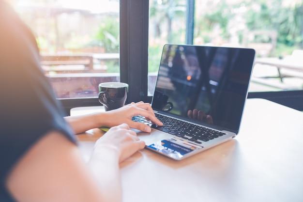 Frauenhand benutzt eine laptop-computer im büro. auf der tabelle gibt es eine kreditkarte.