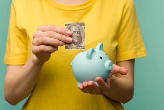Frauenhand, die 100 dollar in schweinchen setzt, um geld, reichtum und finanzkonzept zu sparen