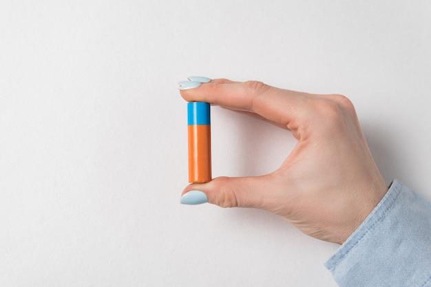Frauenhand, die aa-alkalibatterien auf weißem hintergrund hält. generischer akku
