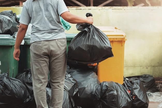 Frauenhand, die abfall in der schwarzen tasche hält, damit innen säubert, um wegzuwerfen